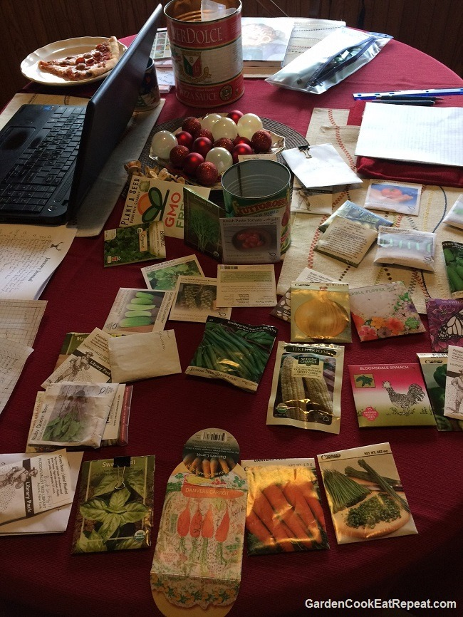 A messy dining table full of seed packs!